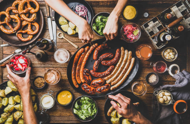 bavarian sausages, snacks and beers for octoberfest dinner party - baviera foto e immagini stock