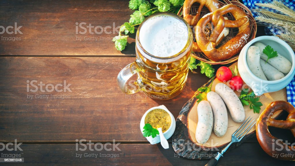 Bavarian sausages with pretzels, sweet mustard and beer mug on rustic wooden table stock photo