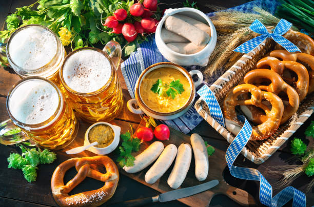 bavarian sausages with pretzels, sweet mustard and beer mugs on rustic wooden table - baviera foto e immagini stock