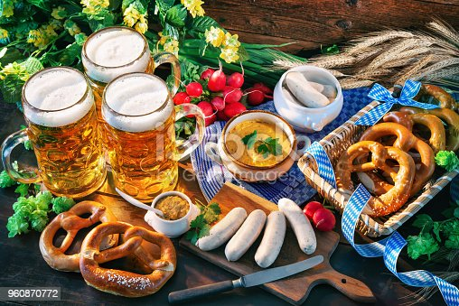 Bavarian sausages with pretzels, sweet mustard and beer mugs on rustic wooden table. Oktoberfest menu