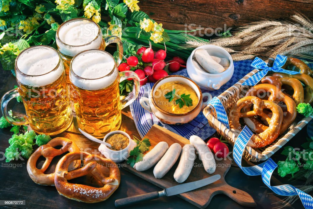 Bavarian sausages with pretzels, sweet mustard and beer mugs on rustic wooden table stock photo