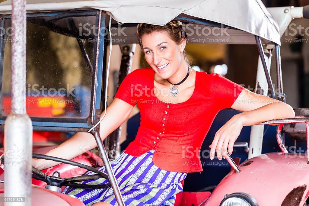 Bavarian woman with Dirndl dress driving tractor stock photo