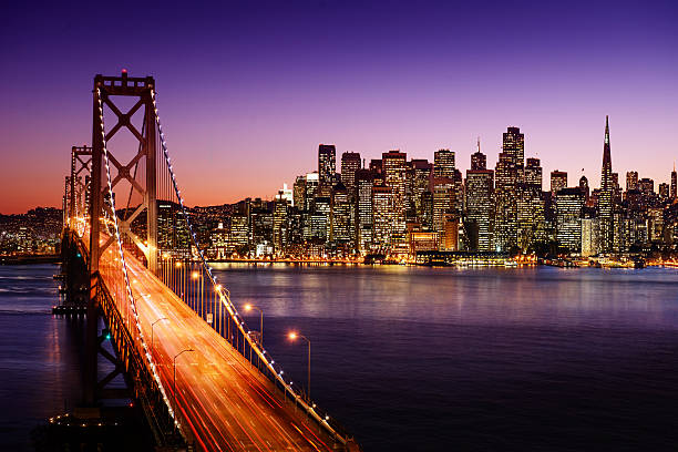 bay bridge and san francisco skyline at sunset - skyline stock photos and pictures