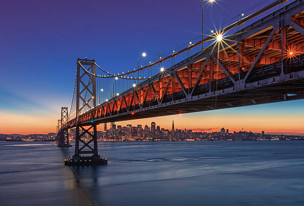bay bridge and san francisco skyline at sunset - international landmark stock photos and pictures