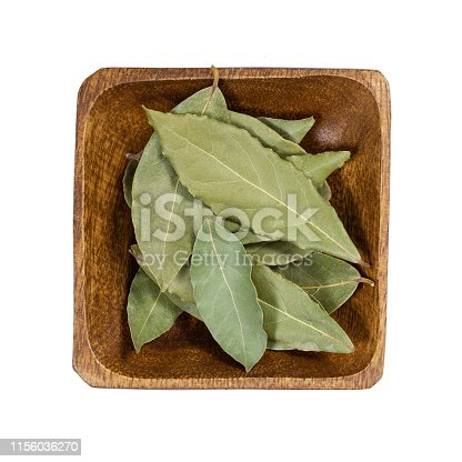 Bay leaf in wooden bowl isolated on white background. Top view.
