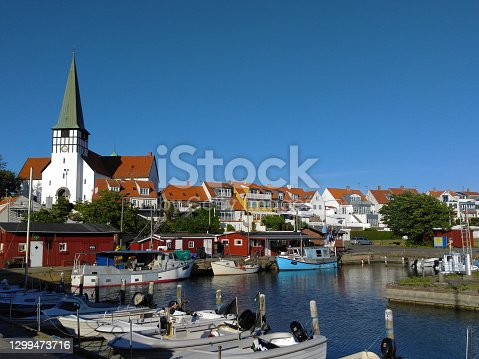 Scandinavian bay with boats, white church and houses with red roof