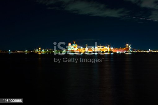 istock Bay of water at night with oil tanker at oil refainery port and city skyline, background with copy space 1164009886