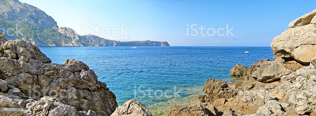 Bay panorama with blue ocean, rocks and mountains stock photo