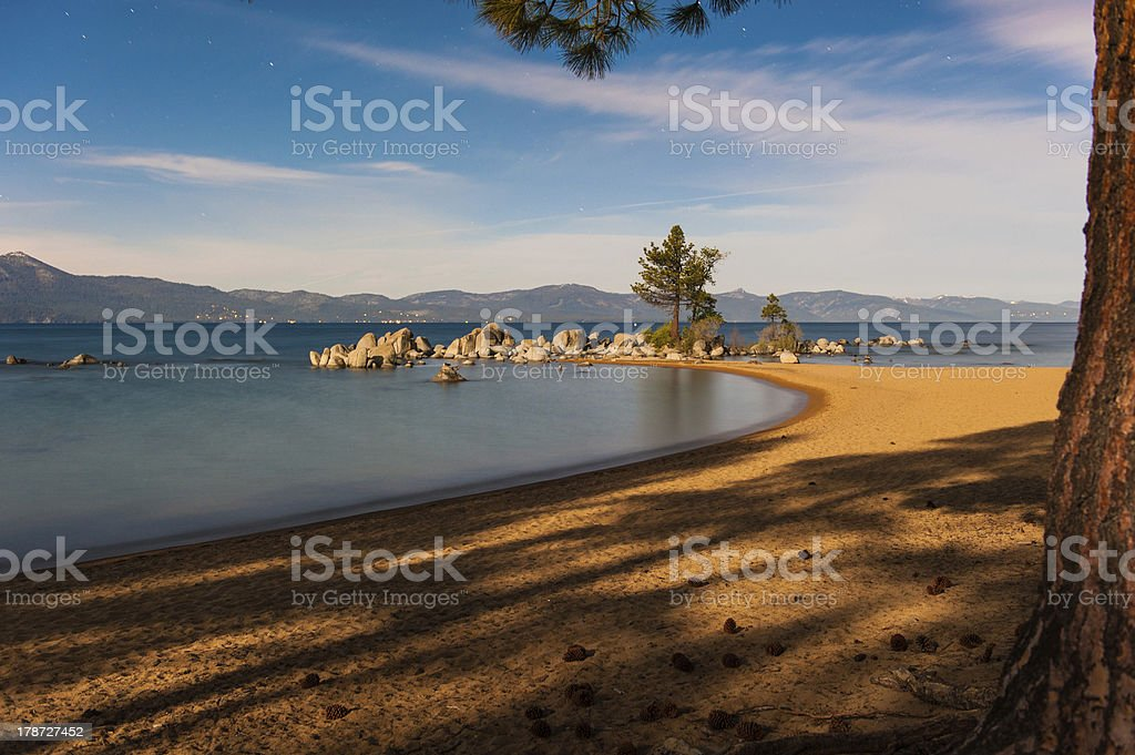 Bay with boulders and pine tree at night royalty-free stock photo