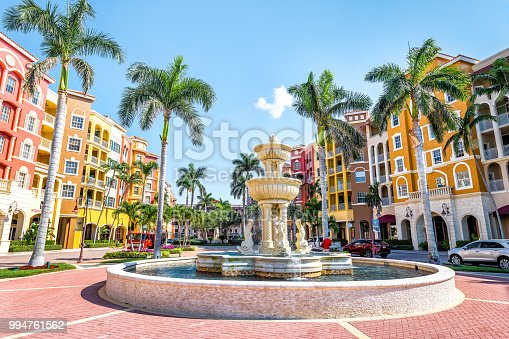 Naples, USA - April 30, 2018: Bayfront condos, condominiums colorful, multicolored, multi-colored buildings with fountain, water, palm trees, blue sky in residential community