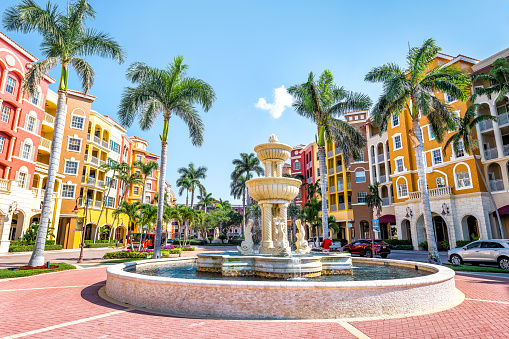 istock Bayfront condos, condominiums colorful, multicolored, multi-colored buildings with fountain, water, palm trees, blue sky in residential community 994761562