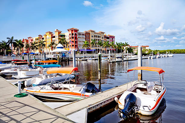 Bayfront Dock and Boats overlooking Naples Bay area with condominiums and shops in background. naples florida stock pictures, royalty-free photos & images