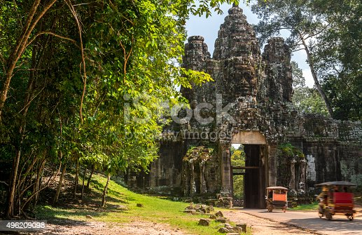 Magnificent ancient gate leading to Angkor Thom in Cambodia. Angkor Thom temple belongs to the Angkor Wat Heritage site; on the picture two tuk yuk vehicles drive tourist passengers.