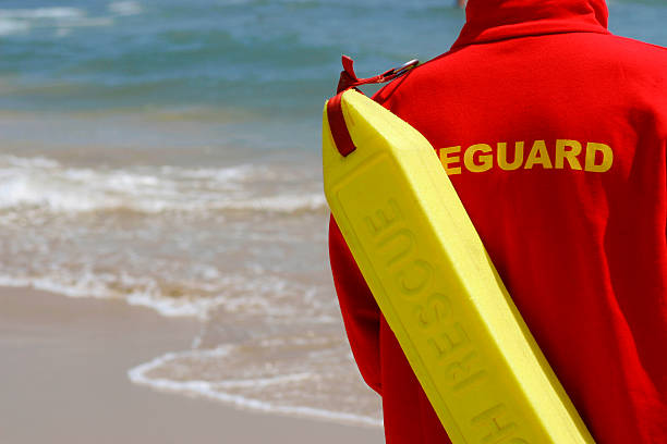 Baywatch Lifeguard With Float At A Beach A lifeguard complete with rescue float monitors their beach lifeguard stock pictures, royalty-free photos & images