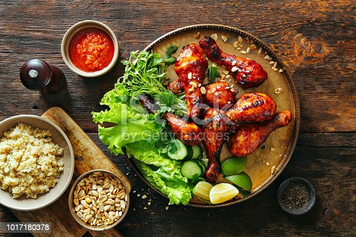 Barbecue chicken legs with barbecue sauce, vegetables, nuts and quinoa