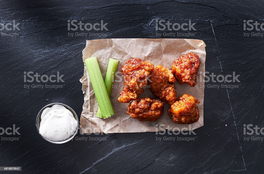 bbq chicken hot wings on parchment paper with ranch and celery shot...