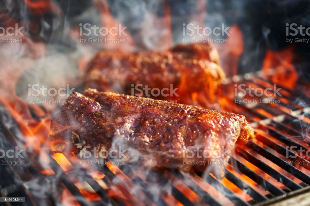 bbq pork ribs cooking on flaming grill stock photo