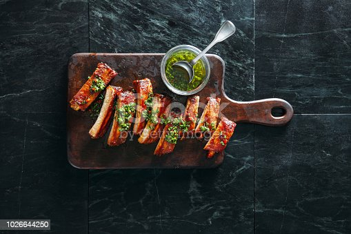 Grilled pork ribs with chimichurri and herbs on dark background