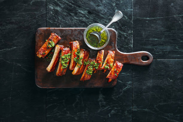 Bbq pork ribs Grilled pork ribs with chimichurri and herbs on dark background pork stock pictures, royalty-free photos & images