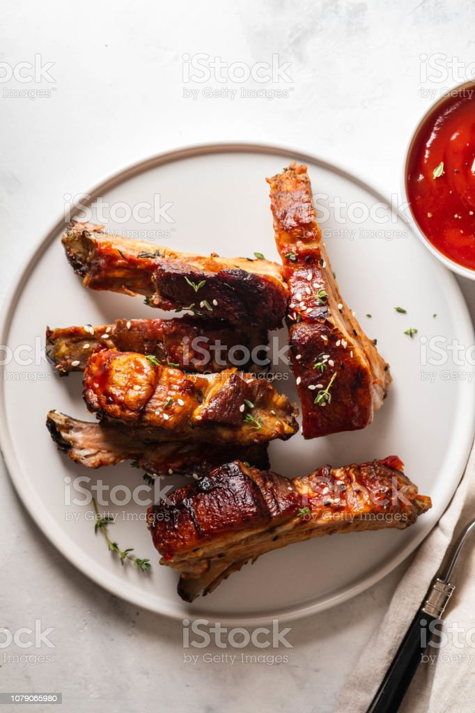 Bbq pork ribs with chili sauce on white plate. Pork ribs on slate...