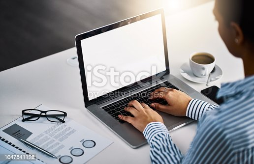 Closeup shot of an unrecognizable businesswoman working on a laptop in an office