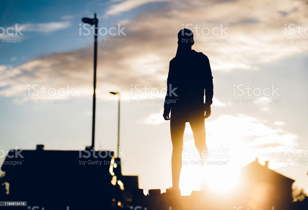 Be a winner Silhouette of young athletic confident woman at sunset. Achievement Stock Photo