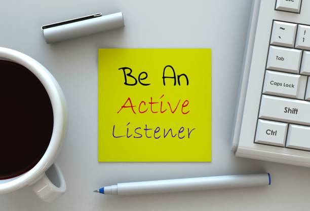 Be An Active Listener, message on note paper, computer and coffee on table stock photo