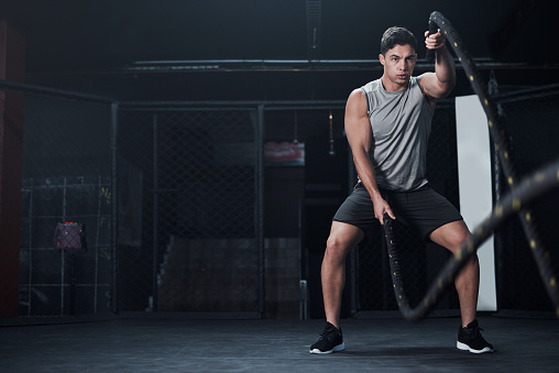 Shot of a young man working out with battle ropes at a gym