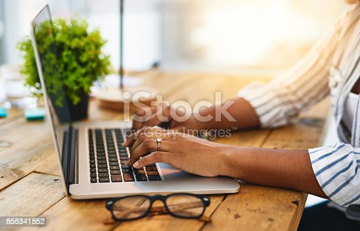 Cropped shot of a woman using her laptop on a wooden table
