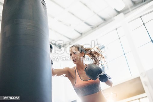 Shot of an attractive young woman working out with a punching bag at the gym