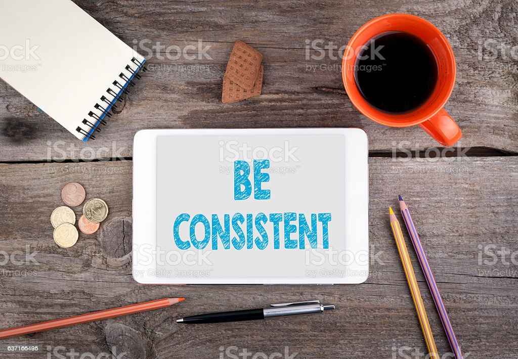 Be Consistent. Tablet device on a wooden table stock photo