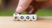 Be cool and not a fool. Hand is turning a dice and changes the word