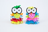 Creativity and imagination. Two colorful owls made from toilet paper roll and colored paper sheets isolated on white background. Decorative handmade toys.