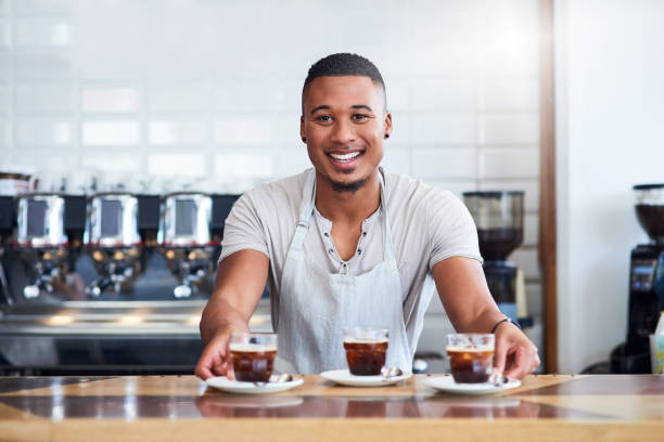 Be daring enough to try these shots! Shot of a barista serving beverages in a coffee shop barista stock pictures, royalty-free photos & images