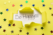 Be happy phrase showing up under torn yellow paper