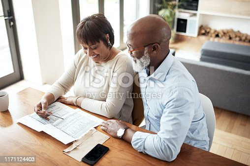 Shot of a mature couple going over paperwork together at home