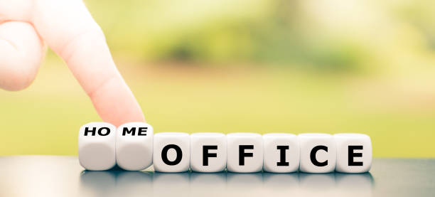 """Be in home office during the corona crisis. Hand turns dice and changes the expression """"office"""" to """"home office"""". stock photo"""
