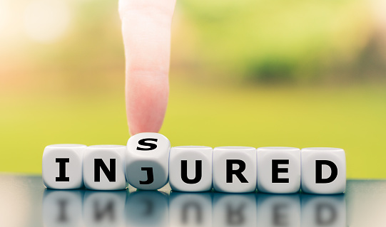 istock Be insured when injured. Hand turns a dice and changes the word injured to insured. 1199246768