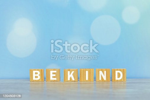 Inspirational words on wooden blocks - Be kind. On vintage soft blue bokeh background. Kindness motivational quote concept.