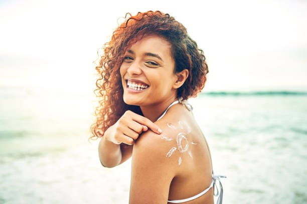 Be like me, apply sunscreen Cropped portrait of an attractive young woman pointing at sunscreen on her back at the beach suntan lotion stock pictures, royalty-free photos & images