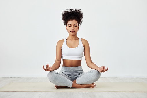 Shot of a fit young woman meditating at home