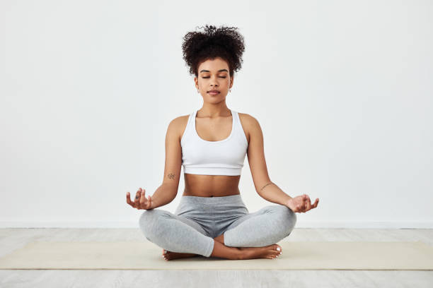 Be mindful of how awesome you are Shot of a fit young woman meditating at home zen stock pictures, royalty-free photos & images