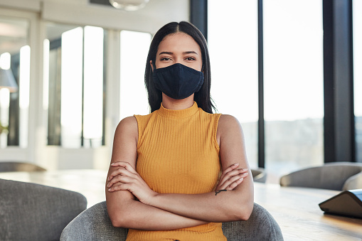 Portrait of a confident masked young businesswoman in the boardroom of a modern office