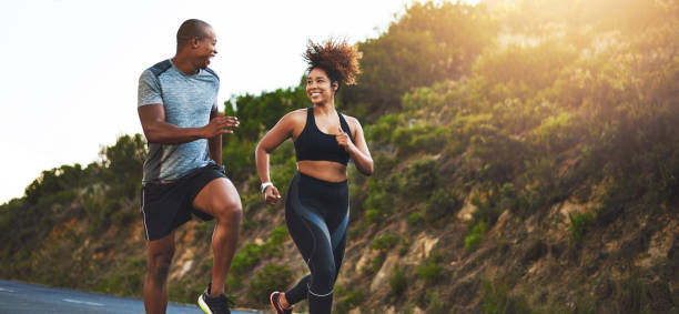 Be strong, you never know who you're inspiring Shot of a young couple out running together cardiovascular exercise stock pictures, royalty-free photos & images