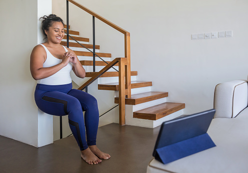 Portrait shot of an attractive Malaysian woman doing wall sit exercise in her living room during Covid 19 pandemic
