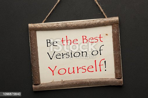 Best Version Of Yourself text on wooden sign hanging on a rope on black background. Motivational concept