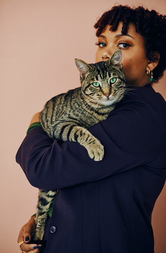 Shot of a beautiful young woman holding her cat while posing against a plain background