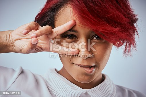 Studio shot of a beautiful young woman showing the peace gesture over her eye
