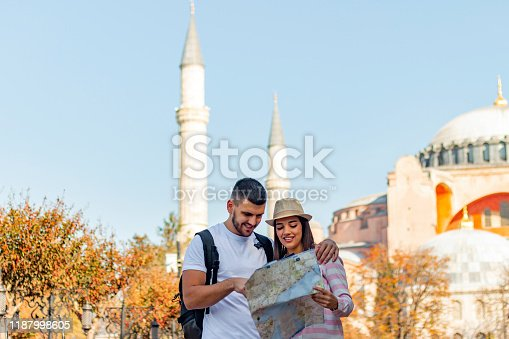 Front view of young smiling beautiful traveler girl is watching a map. Travel, tourism, sightseeingIstanbul the capital of Turkey, eastern tourist city.