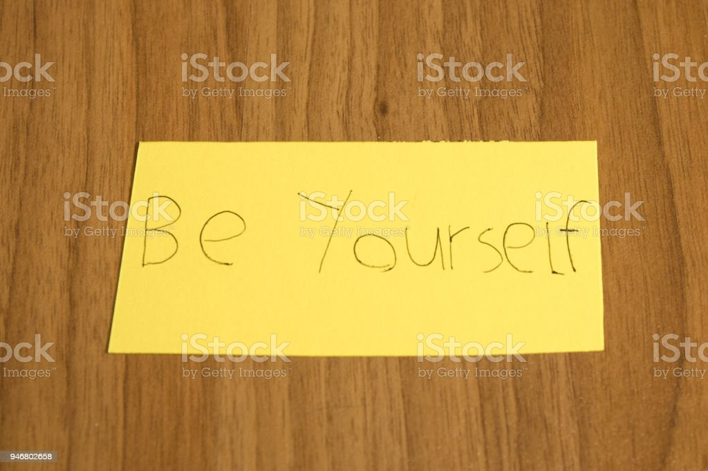 Be yourself handwrite on a yellow paper with a pen on a table composition stock photo